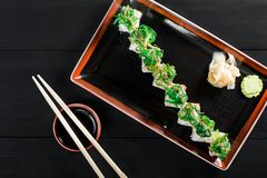 Sushi Roll - Maki Sushi with sea kale, Crab meat, avocado, cream cheese and sesame on dark wooden background. Top view. Japanese cuisine royalty free stock images