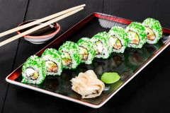 Sushi Roll - Maki Sushi with green caviar, Crab meat, avocado and cream cheese on dark wooden background. Top view. Japanese cuisine royalty free stock photo