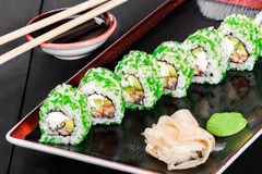 Sushi Roll - Maki Sushi with green caviar, Crab meat, avocado and cream cheese on dark wooden background. Royalty Free Stock Photo