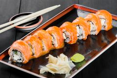 Sushi Roll - Maki Sushi made of salmon, cucumber, avocado and cream cheese on dark wooden background. Top view. Japanese cuisine royalty free stock photography