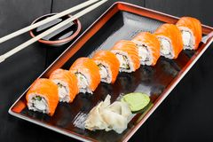 Sushi Roll - Maki Sushi made of salmon, cucumber, avocado and cream cheese on dark wooden background. Top view. Japanese cuisine stock photos
