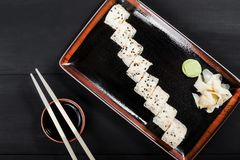 Sushi Roll - Maki Sushi made of salmon, orange, avocado and cream cheese on dark wooden background. Top view. Japanese cuisine royalty free stock images