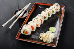 Sushi Roll - Maki Sushi made of salmon, orange, avocado and cream cheese on dark wooden background. Top view. Japanese cuisine royalty free stock photos