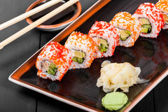 Sushi Roll - Maki Sushi with red caviar, Crab meat, avocado, cucumber and cream cheese on dark wooden background. Royalty Free Stock Image