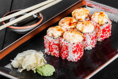 Sushi Roll - Maki Sushi with red caviar, eel, avocado and cheese on dark wooden background. Royalty Free Stock Image