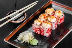 Sushi Roll - Maki Sushi with red caviar, eel, avocado and cheese on dark wooden background. Top view. Japanese cuisine stock images