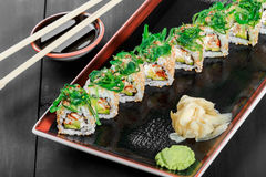 Sushi Roll - Maki Sushi with sea kale, Crab meat, avocado, cream cheese and sesame on dark wooden background. Stock Image