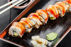 Sushi Roll - Maki Sushi with smoked eel, cucumber, avocado and cream cheese on dark wooden background. Royalty Free Stock Images