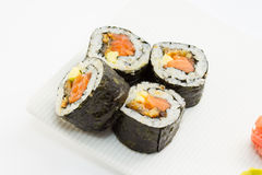 Sushi roll in nori with ginger and wasabi on white plate Stock Photos