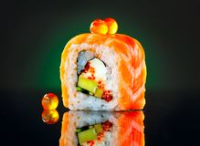 Sushi roll over black background. California sushi roll with salmon, vegetables, flying fish roe closeup Royalty Free Stock Photos