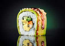 Sushi roll over black background. Sushi roll with eel, tofu, vegetables and avocado closeup. Japanese food stock photography