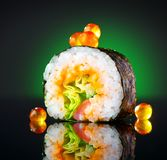 Sushi roll over black background. Sushi roll with tuna, vegetables, flying fish roe and caviar closeup Stock Image