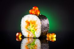 Sushi roll over black background. Sushi roll with tuna, vegetables, flying fish roe and caviar closeup Royalty Free Stock Images