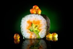 Sushi roll over black background. Sushi roll with tuna, vegetables, flying fish roe and caviar closeup Stock Photos