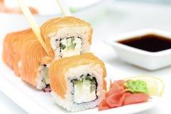 Sushi roll Philadelphia in chopsticks Royalty Free Stock Photos