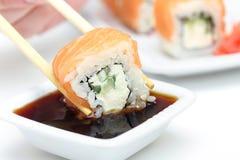 Sushi roll Philadelphia in chopsticks Royalty Free Stock Photo