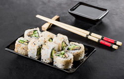 Sushi Roll on a plate. Chopsticks and soy on a black background Stock Photos