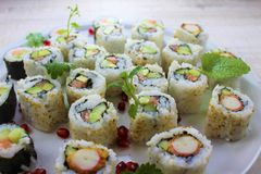 Sushi roll on a round white plate with mint leaf and pomegranate royalty free stock photos