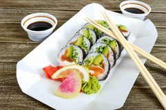 Sushi roll with salmon, avocado, cream cheese, leek, cucumber, tobiko caviar, served on a paper plate. stock photos