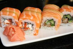 Sushi roll with salmon, avocado, philadelphia cheese on black background. Sushi menu. Japanese food royalty free stock photography