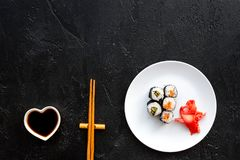 Sushi roll with salmon and avocado on plate with soy sauce, chopstick, wasabi on black background top view copyspace royalty free stock photo