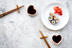 Sushi roll with salmon and avocado on plate with soy sauce, chopstick, wasabi on grey stone background top view royalty free stock photos