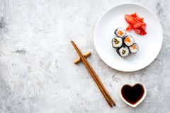 Sushi roll with salmon and avocado on plate with soy sauce, chopstick, wasabi on grey stone background top view Stock Photography
