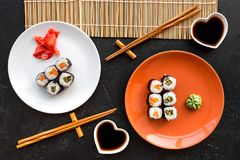 Sushi roll with salmon and avocado on plate with soy sauce, chopstick, wasabi on mat on black background top view stock photography