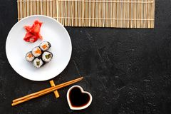 Sushi roll with salmon and avocado on plate with soy sauce, chopstick, wasabi on mat on black background top view stock photo