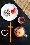 Sushi roll with salmon and avocado on plate with soy sauce, chopstick, wasabi near tea pot on black background top view royalty free stock image