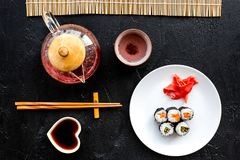 Sushi roll with salmon and avocado on plate with soy sauce, chopstick, wasabi near tea pot on black background top view Stock Images