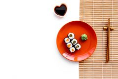 Sushi roll with salmon and avocado on plate with soy sauce, chopstick, wasabi on mat. White background Top view Stock Photo