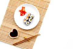 Sushi roll with salmon and avocado on plate with soy sauce, chopstick, wasabi on mat. White background Top view Royalty Free Stock Photos