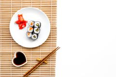 Sushi roll with salmon and avocado on plate with soy sauce, chopstick, wasabi on mat. White background Top view Stock Photos