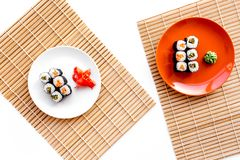 Sushi roll with salmon and avocado on plate with soy sauce, chopstick, wasabi on mat. White background Top view royalty free stock images