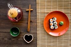 Sushi roll with salmon and avocado on plate with soy sauce, chopstick, wasabi on wooden table background top view Stock Photo