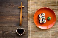 Sushi roll with salmon and avocado on plate with soy sauce, chopstick, wasabi on wooden table background top view. Sushi roll with salmon and avocado on plate royalty free stock photography