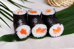 Sushi roll salmon chives mini kappa maki in the still life on a tropical leaves Royalty Free Stock Image