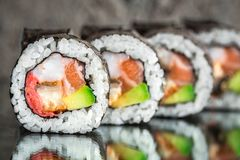 Sushi roll with salmon, shrimps and avocado. Over cocnrete background Stock Photography