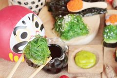 Sushi roll with seaweed salad and shrimp eggs. Royalty Free Stock Photography