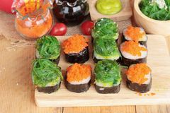 Sushi roll with seaweed salad and shrimp eggs. Royalty Free Stock Image