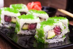 Sushi roll set in green caviar with ginger, soy sauce, towel and chopsticks Stock Photo
