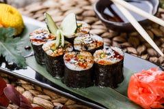 Sushi-Rolle - Maki Sushi mit geräuchertem Aal, Gurke, Avocado und indischem Sesam auf schwarzem Stein auf der Bambusmatte verzier Stockbild