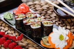 Sushi-Rolle - Maki Sushi mit geräuchertem Aal, Gurke und Avocado auf schwarzem Stein auf der Bambusmatte verziert mit Blumen Lizenzfreies Stockfoto