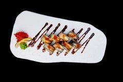 Sushi-Rolle mit Aal- und Lachskaviar Beschneidungspfad eingeschlossen Lokalisiert auf einem schwarzen Hintergrund Lizenzfreie Stockbilder