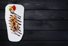 Sushi-Rolle mit Aal- und Lachskaviar Beschneidungspfad eingeschlossen Schwarzer hölzerner Hintergrund Lizenzfreies Stockfoto