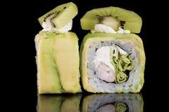 Sushi-Rolle mit Krebsfleisch, Kiwi und Avocado über schwarzem backgrou Stockfotos