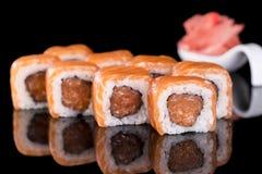 Sushi-Rolle mit Lachsen über schwarzem Hintergrund mit Reflexion Stockbild