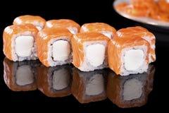 Sushi-Rolle mit Lachsen über schwarzem Hintergrund mit Reflexion Lizenzfreie Stockfotografie