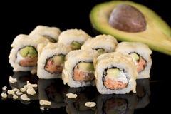 Sushi-Rolle mit Lachsen und Avocado über schwarzem Hintergrund mit r Lizenzfreies Stockbild